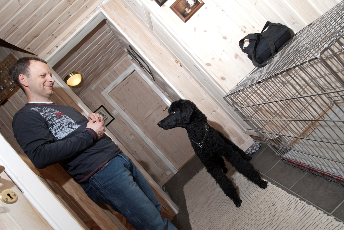 Hunden Pedro sammen med sin eier ved siden av et hundebur i hjemmet.