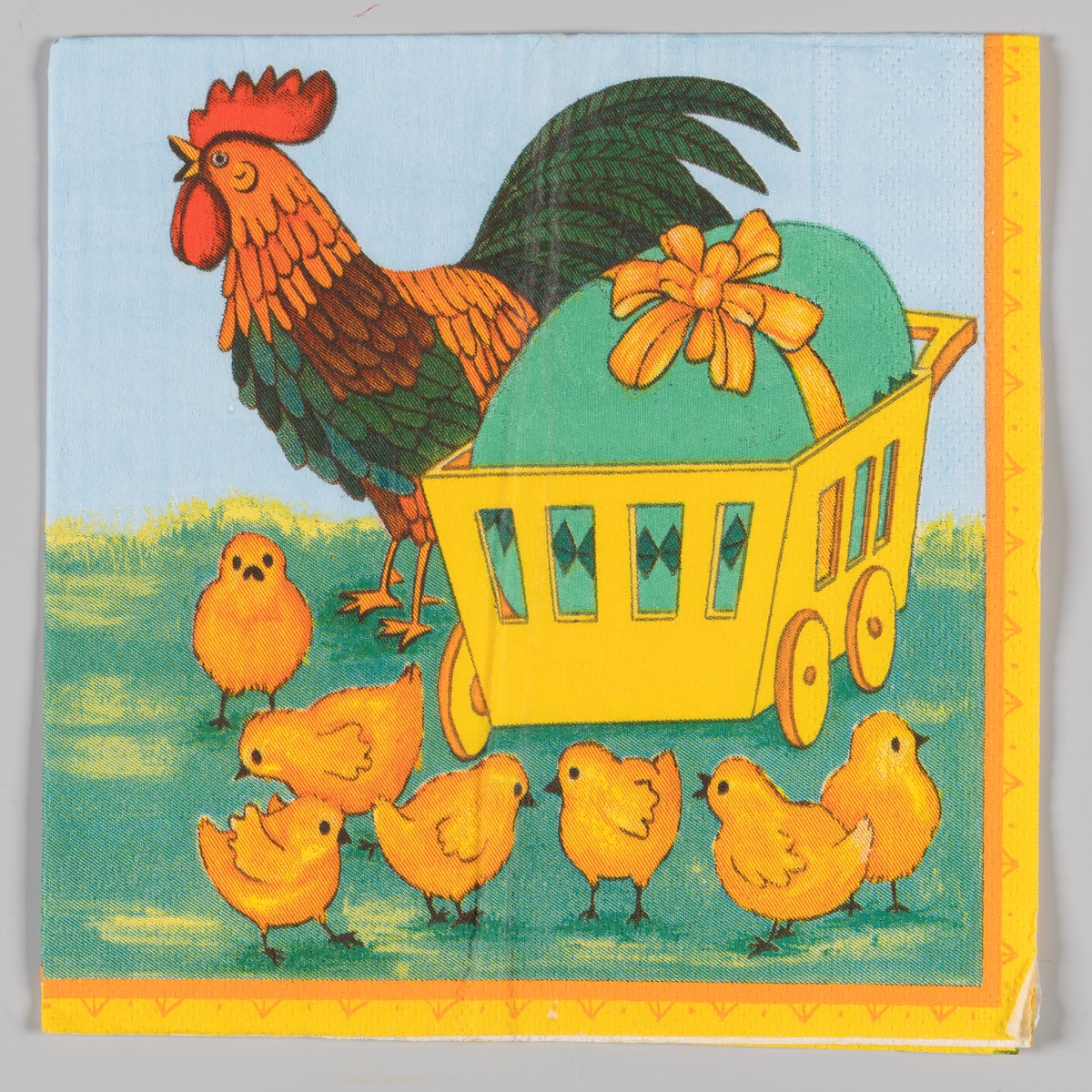 En trillevogn med et stort grønt påskeegg med sløyfe. En hane og en flokk med kyllinger.
