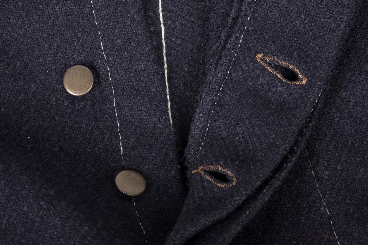 Fangedraktbukse for menn fra Grini i tykt mørkeblått ullstoff (kypert), med hvite kontrastsømmer. Buksa har større hull (musespist).