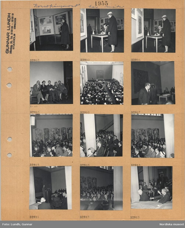 """Motiv: Konstfrämjandet har möte ; Interiör med kvinnor som tittar på konst på en utställning, en man sitter vid ett skrivbord och skriver och en kvinna står bredvid, en grupp män och kvinnor sitter på en soffa """"X-et"""" troligen konstnären Sven X-et Erixson, en man står i en talarstol och kvinnor och män som håller ett papper sitter i stolar vid ett möte."""