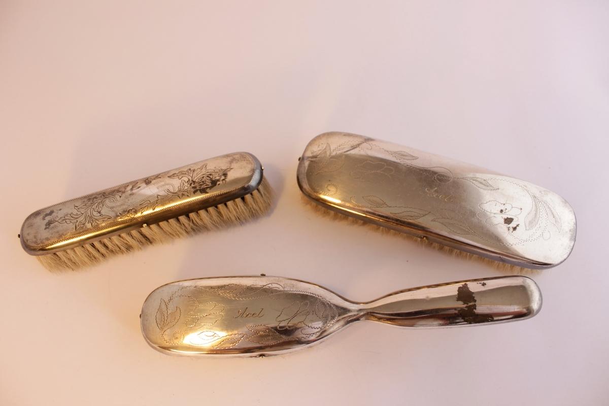 """Borstgarnityr bestående av tre borstar en (a) hårborste, två klädesborstar (b-c). Naturborst. Borstarna är klädda i nysilver som har ingraverade stiliserade blommönster. Hårborsten och den ena klädborsten har namnet """"Axel"""" ingraverat på ovansidan. Själva borsthuvudena är tillverkade av trä och sedan har en plåt av nysilver spikats på."""