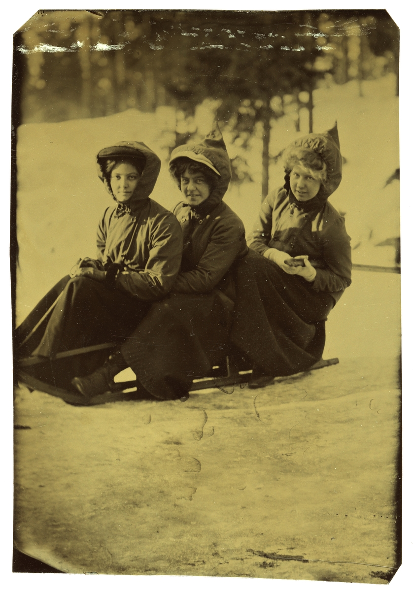 Betsy Gude (Schirmer) med venninner på en kjelke i Holmenkollen.   Foran sitter Stephanie Banks fra Irland, en ukjent pike i midten og Betsy bakerst.