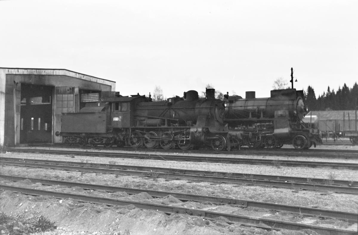 Damplokomotiv type 24b nr. 264 ved lokomotivstallen på Eina stasjon. Bak et damplokomotiv type 31b.