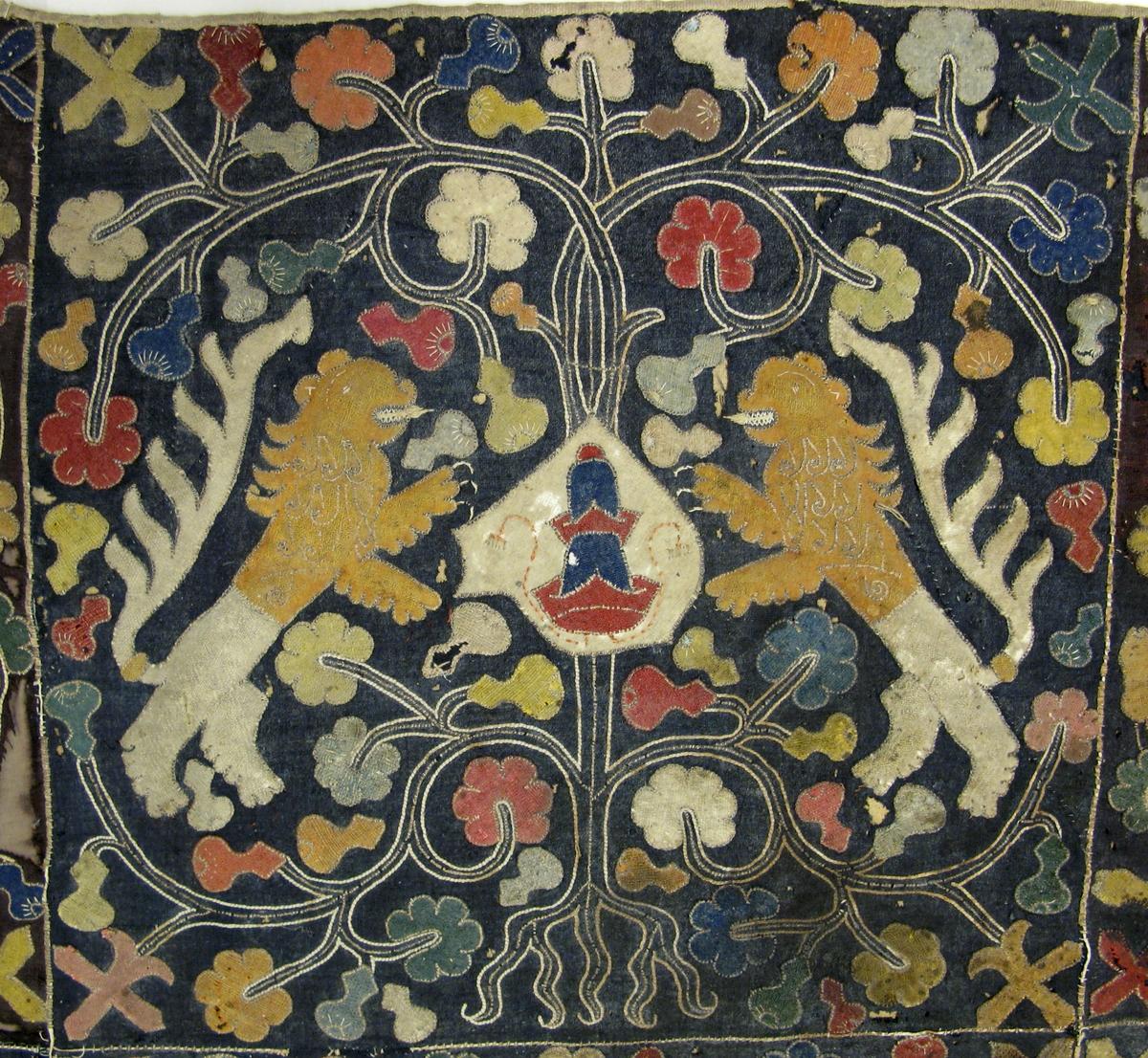 Eventuellt en brudpäll (se nedan) - en större applikation av olikfärgade kypertvävda ylletyger, bestående av tolv kant i kant hopsydda kvadrater i rödbrunt, blått eller svart.  Alla kvadraterna har applicerade motiv av två olika vapensköldar (varannan kvadrat) flankerade av två motställda stående lejon med röda eller senapsgula överkroppar, omgivna av träd med krona och rötter samt olikfärgade växter och blad. Lejonen är i relief med linblånor som stoppning. Alla färgerna är fortfarande mestadels klara. All teckning är utförd med ljus lintråd samt med förgyllda smala skinnremsor, båda nersydda med läggsömmar. Förgyllningen på skinnremsorna har till stora delar försvunnit. Alla skarvar emellan kvadraterna är täckta med samma förgyllda skinnremsor. Hela textilen är fodrad med tuskaftvävd linneväv vari broderierna är nersydda, Enlig Branting/Lindblom (1928:60) är applikationen eventuellt en brudpäll på grund av de båda vapensköldarna - en med tre gula rosor inuti blå rand (Rosenbjelke) samt en med en blå och röd judisk mössa (Kruse av Elghammar).  Osäkert om detta stämmer då det inte går att bekräfta i modernare forskning om adelsvapen.
