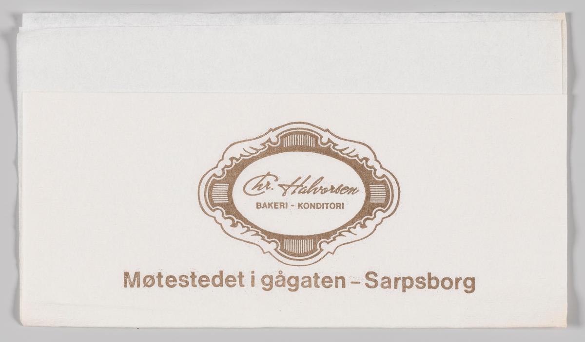 En ramme i rokokkostil med en reklametekst for Chr. Halvorsen Bakeri og Konditori i Sarpsborg.  Chr. Halvorsen Bakeri og Konditori i Sarpsborg ble startet i 1888 og opphørte i 2003 etter 115 år i drift. Firmaet var i alle år drevet av generasjoner av Halvorsen familien.