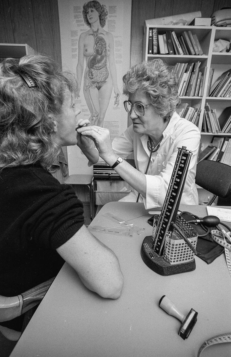 Illustrasjonsfoto. Besøk hos legen, måler blodtrykket og kikker i halsen. Kvinnelig lege og pasient.