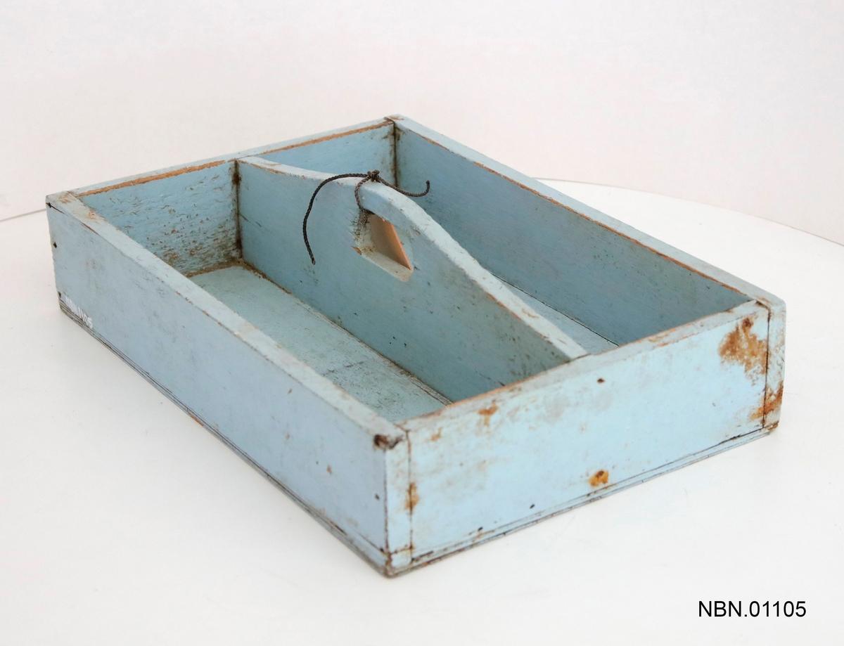 Trekasse for kniv og bestikk. Rektangulær form, med to rom. Kasse er åpen, og midtdeleren er bueformet med et håndtak. Turkis malt.