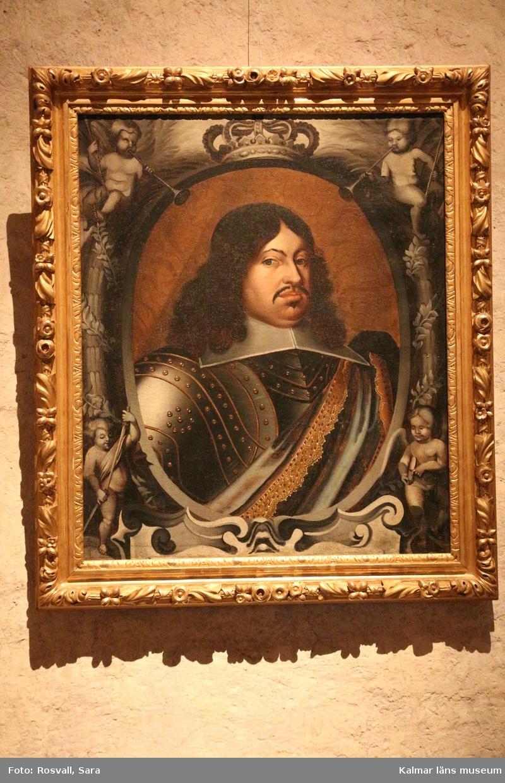 Porträtt, bröstbild av Karl X Gustav i rustning. Vit, stärkt krage, över vänstra axeln ett draperi eller värjgehäng. Oval målad inramning med putti och lagerkransar. Över ovalen en krona, nedan början till textkartusch.