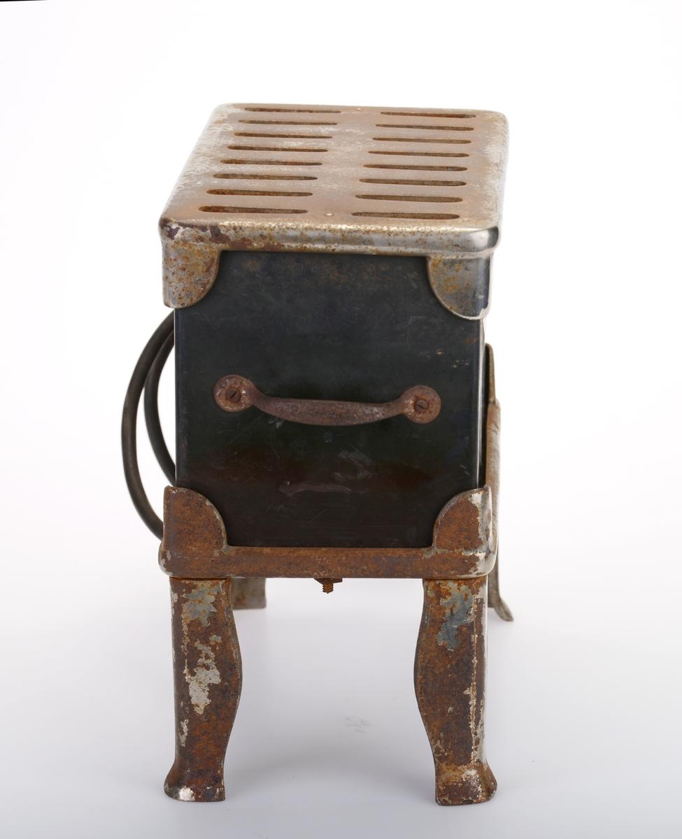 """En firkantet liten elektrisk ovn laget av støpejern som er delvis svartlakkert og delvis forkrommet. Den fire små føtter slik at den står 10cm over bakken. Føttene er på et stativ som selve ovnen står i. Stativet og føttene er laget av støpejern som er forkrommet. På toppen og på undersiden er det en rist av støpejern som er forkrommet. Det er 16 hull i risten. På toppristen er det tunger i hvert hjørne som fester den til selve ovnen.  Ovsnakssen er av svartlakkert støpejern. På den ene siden er det skrudd på et skilt med styrke på watt og volt samt navnet på ovnen, se """"Påført tekst/merker"""". Under skiltet er det skrudd på en forkrommet rose som dekor. På undersiden er det festet elektrisk ledning som er kveilet opp på siden. I enden er det et støpsel."""