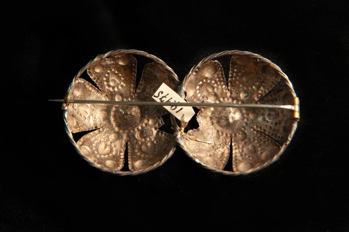 Två hoptvinnade maljor av ciselerat silver med dekor av hjärtan m.m. och med två infattade stenar av rött glas. Maljorna har gjorts om till en brosch.