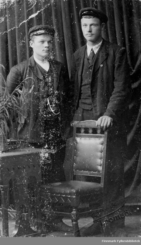 To menn, Olsen og Fikse, fotografert i fotoatelier. Muligens en ung Fredrik Johan Fikse? Far til Fredrik Johan Fikse het Ole Olsen Fikse og var fra Verdalen i Trøndelag, han og kona Maren Dorthea Olsen slo seg ned i Skjøtningberg.  Dette bildet er tatt i Tromsø, se nedre bildehjørne til høyre. Bildeserien FBib.18017-001-018 har tilhørt Gerd Lund Barbala fra Friarfjord.