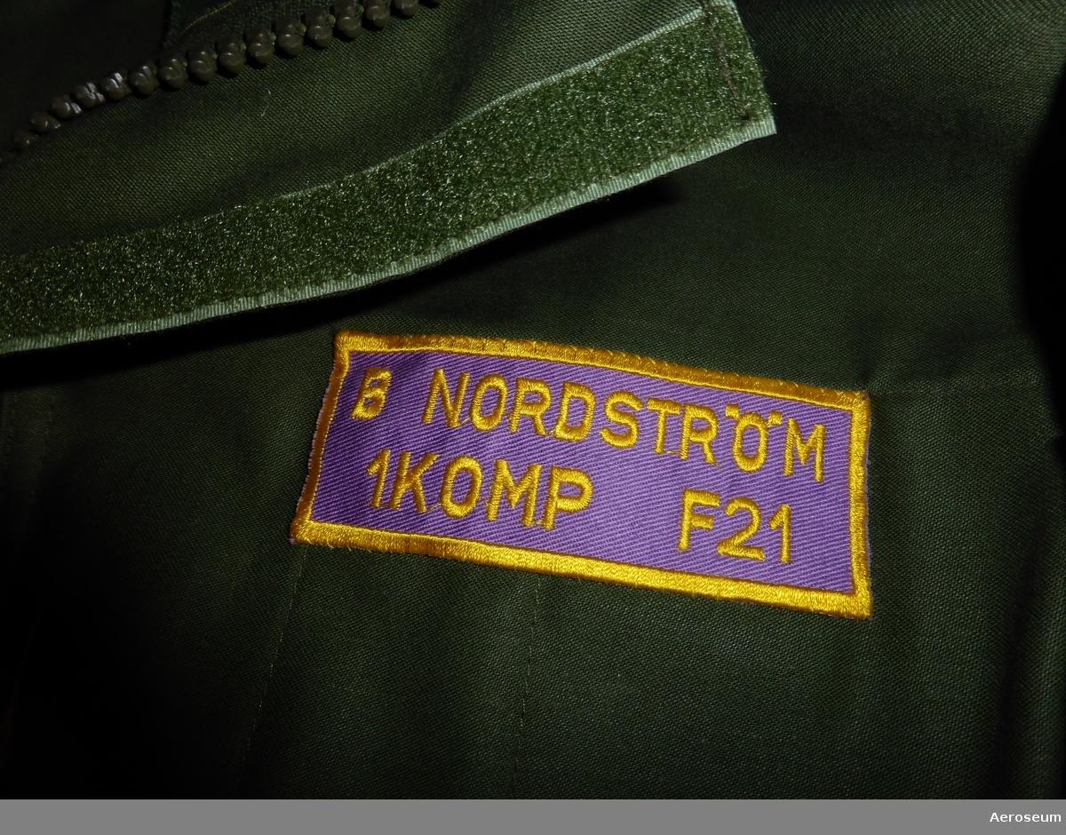 """En mörkgrön overall för färdmekaniker. Denna har använts i svenska flygvapnet och av B. Nordström. Det finns på overallen en namnskylt där det står: """"B NORDSTRÖM 1 KOMP F 21"""". På ena armen finns det ett förbandsmärke där det står """"1 KOMP [bild på ett flygplan, troligtvis Viggen] F 21/SeÖN"""". På andra armen sitter ett vapenslagsmärke som föreställer det svenska flygvapnets."""