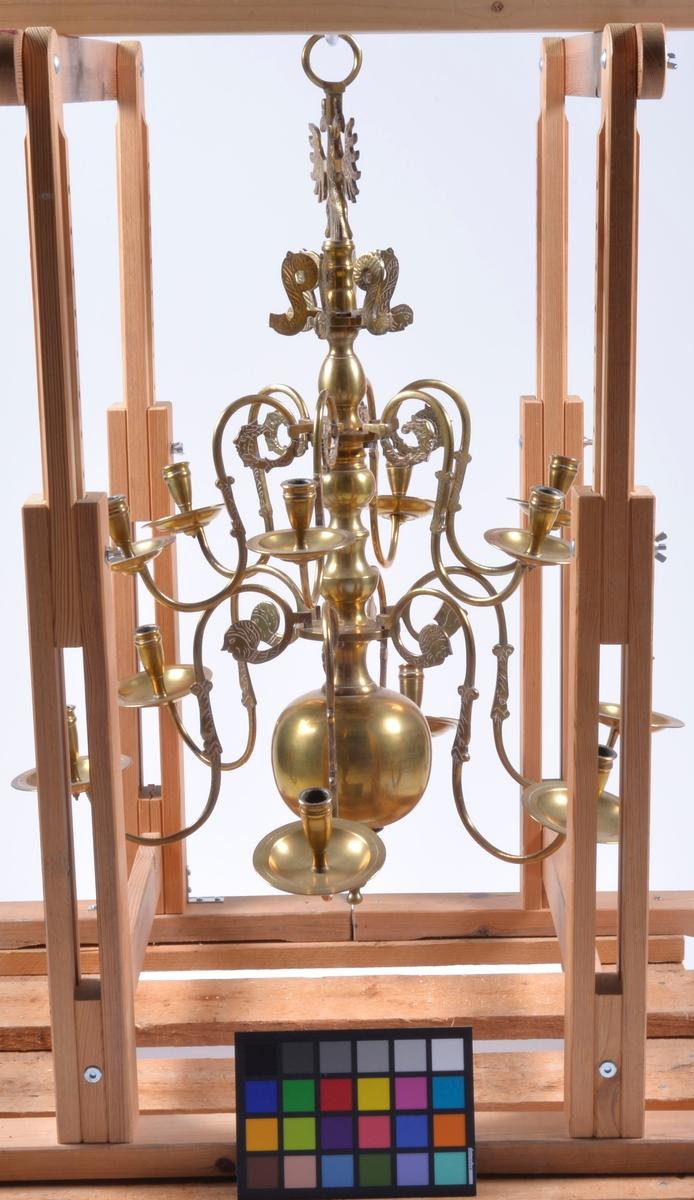 Krönt av dubbelörn. Kronans nedre del prydd med kula (omkrets: 48 cm.) Tolv st. ljusarmar.
