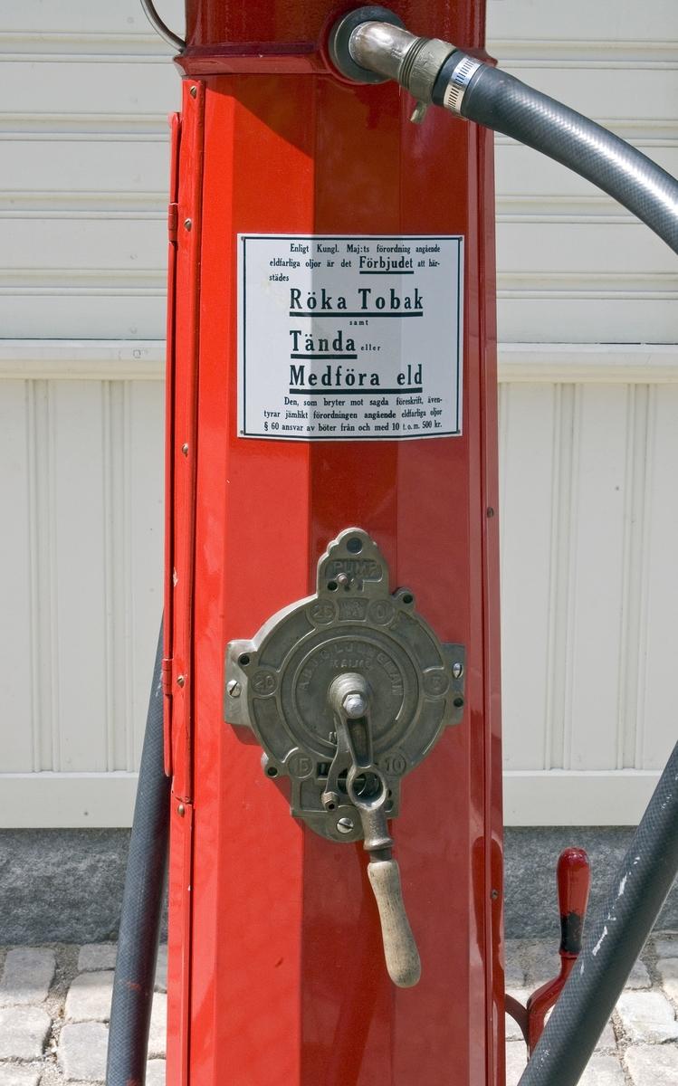 """Bensinpump, fabriksgjord. Överst sitter en glasglob, SKAFOR.0015125 på ett metallfäste.  Under globen en cylinder av glas med mätmekanism och gradering. Därunder kommer det rödlackade pumphuset av stål. På en sida sitter en etikett av metall med text: Enligt Kungl. Maj:ts förordning angående eldfarliga oljor är det Förbjudet [understruket] att härstädes Röka Tobak [understruket] samt Tända [understruket] eller Medföra Eld [understruket]. Den som bryter mot sagda föreskrift, äventyrar jämlikt förordningen angående eldfarliga oljor § 60 ansvar av böter från och med 10 t.o.m. 500 kr."""" Etiketten sitter strax ovanför ett pumphandtag med omgivande dekorativt utformade """"bricka"""" av metall och handtag svarvat av trä. """"Brickan"""" är rund och utformad med graderingar från 0 till 25 med femliters intervaller. Text: PUMP IV-SC 54 A.B. J.C. LJUNGMAN MALMÖ VICI No 6705, ett räkneverk och LITER. Till höger om detta sitter ett annat pumphandtag av rödlackerat stål, fäst nertill. Ovanför etiketten börjar bensinslangen av gummi i ett metallfäste. Den fortsätter i en böj neråt till vänster, runt och upp och avslutas av den utgående kranen av metall, som hänger i ett hål på cylindern. Där bredvid finns också en låsbar lucka."""