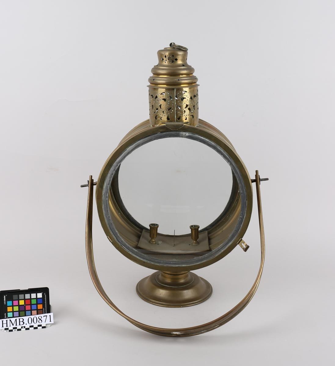 Sirkulær messinglykt på stang i dreid tre. Runde glassdører på for og bakside som kan åpnes. Plass til to stearinlys inni lampen.