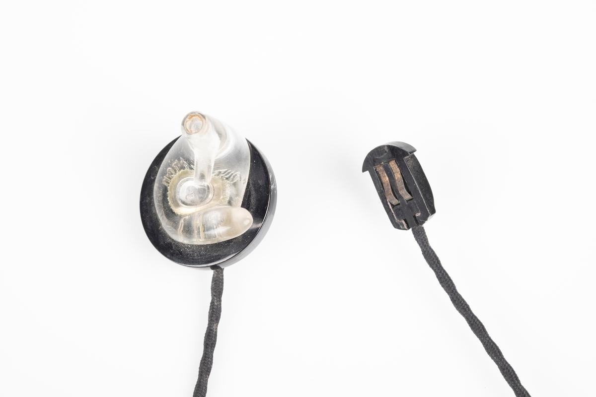 Ørepropper som kobles til radioen. Den har svart flettet ledning og propp i plast som kan fjernes fra ledningen. Den ene proppen mangler.