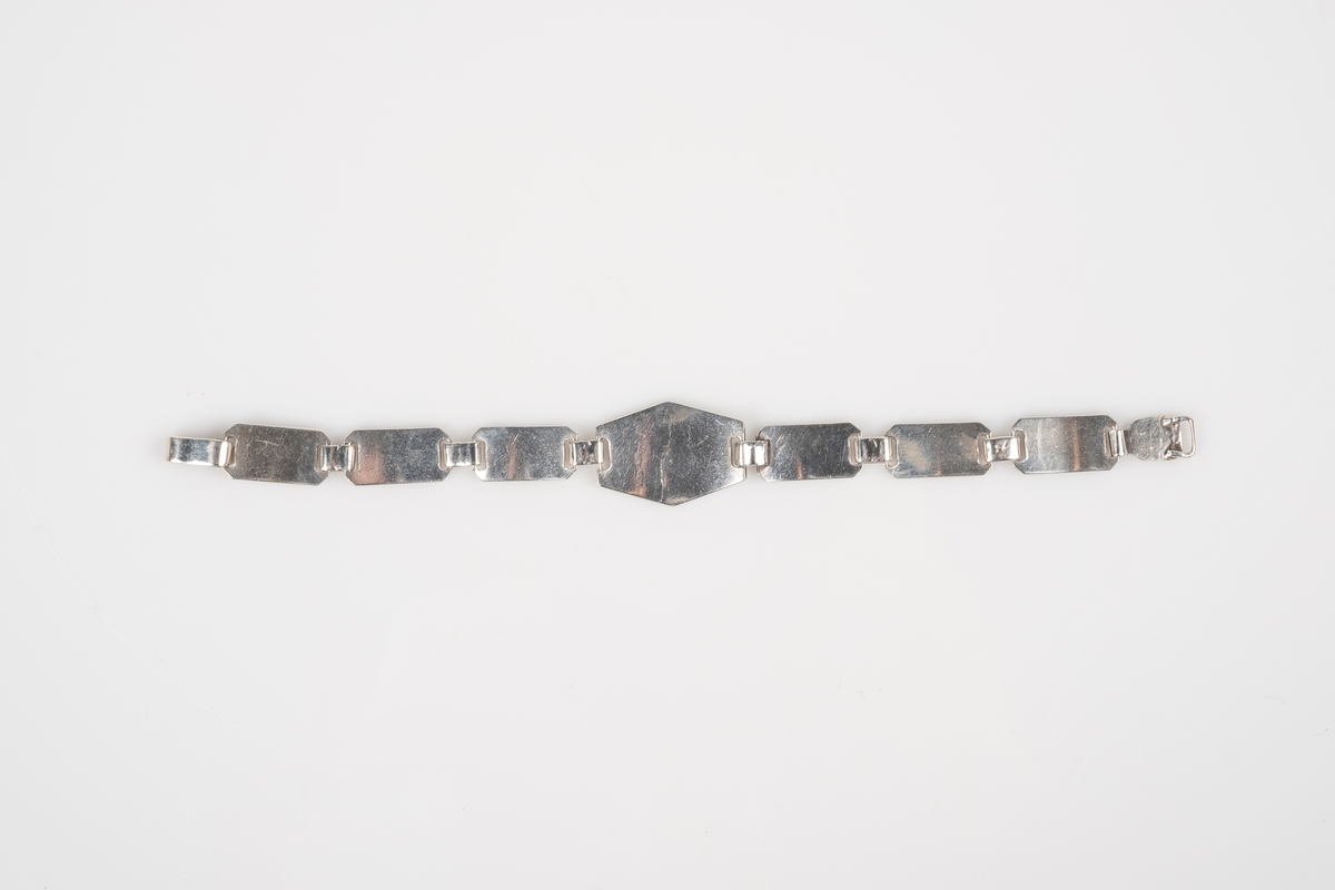 Et sølvarmbånd som består av små plater lenket sammen. Den midtre platen er større enn de andre. Det er inngravinger i 6 av 7 plater. Armbåndet låses med en kroklås. Det er inngravert et vakttårn i den midtre platen, på de mindre platene er det inngravert navn, dato og grinisymbol.