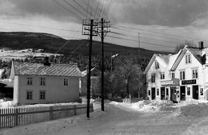 Ringebu. Vålebru. Mæhlums butikk med Lindstad over veien. Stolper med ledninger i alle retninger. Vinter. Speilvendt.