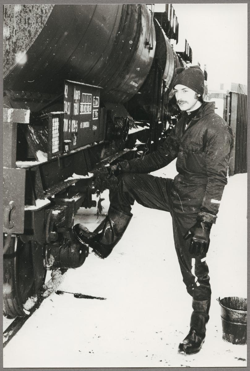 Tomas Karlsson rutinerad oljelossare står mot Statens Järnvägar, SJ Z 42 74 708 3 029-5 tankvagn och putsar sina stövlar.