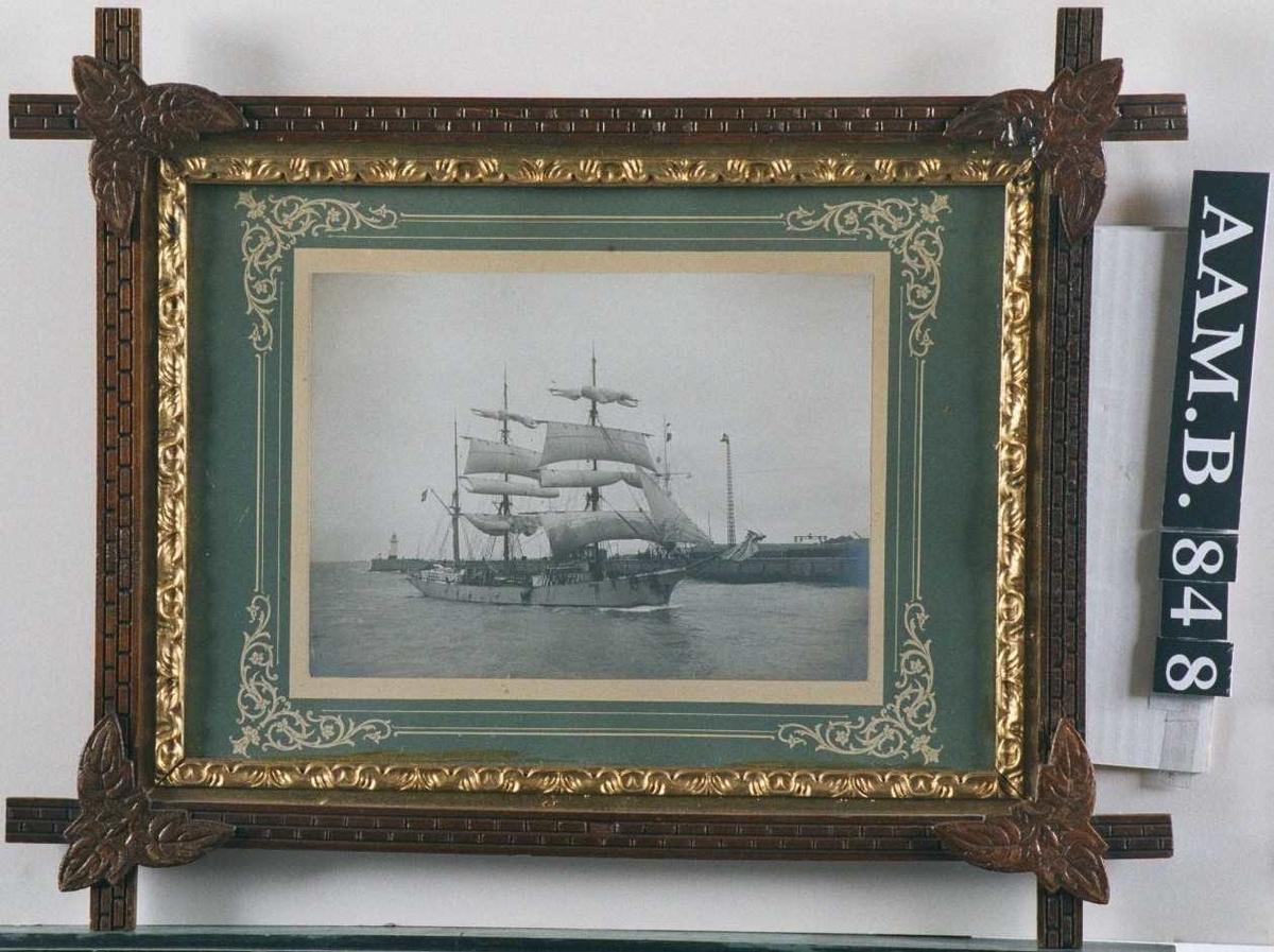 Seilskute som ankommer en havn, skuta er sett fra styrbord side, med redusert seilføring. I bakgrunnen en lang molo med en lysmast th. og en fyrlykt ytterst tv.