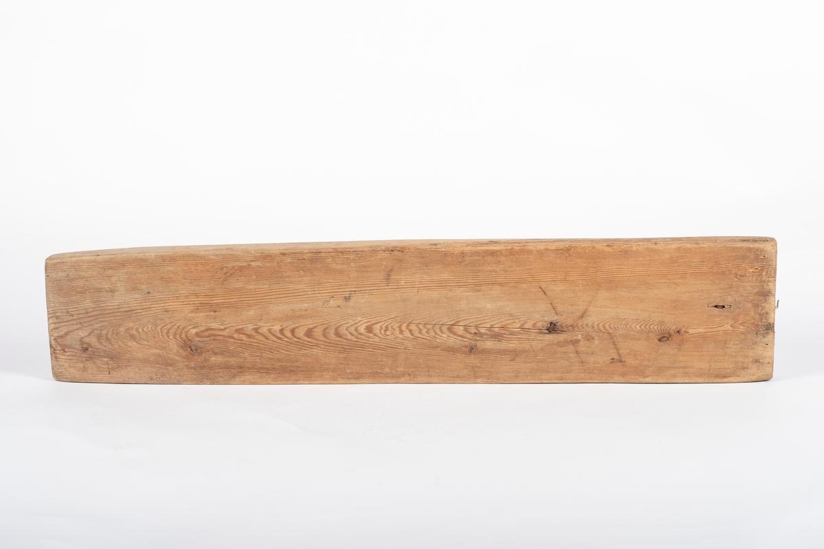 Langt og kraftig manglebrett. Oversiden er vinklet litt oppover med fire kanter, er ikke flat som undersiden. Håndtaket er enkelt, og det er festet til brettet med kraftige metallnagler.  Ved den ene siden av håndtaket ser det ut til å ha sittet noe i lær, for det sitter igjen en lær-rest, festet med to spikre. På kortsiden bak håndtaket er det festet en liten krok.