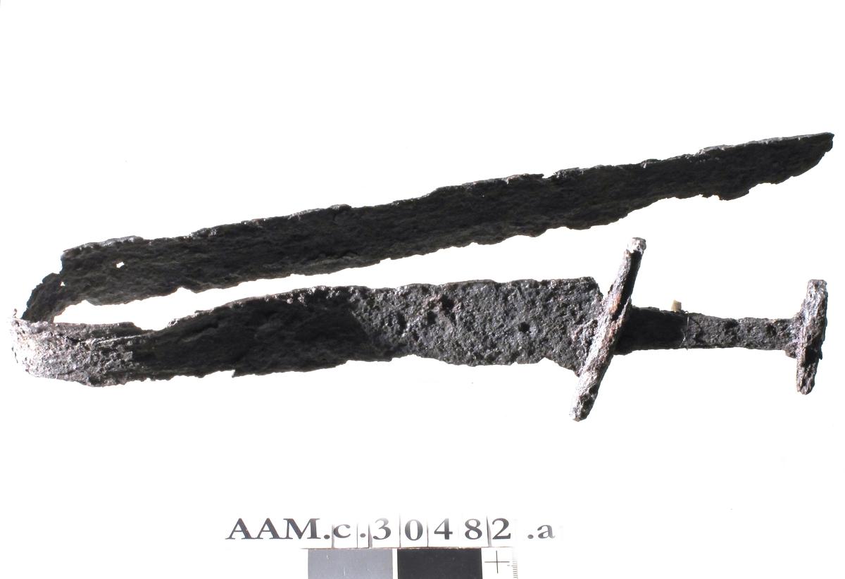 Enegget sverd av jern, som Jan Petersen: Vikingesverd, fig. 98, M-typen, men hjaltene noe smalere. Sammenbøyet. Noe forrustet, men ellers bra bevart. Samlet lengde ca. 84 cm, herav håndtaket 10,9 cm. Hjaltenes lengde 10,6 og 6,8 cm.