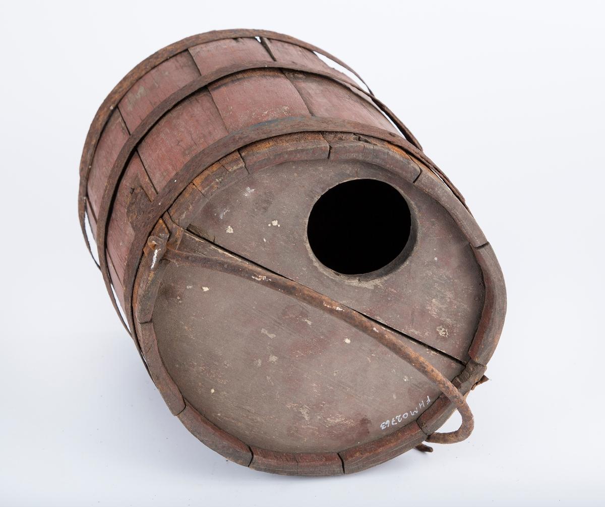 Sylindrisk med lokk og hank. Lagget trebøtte med fast lokk med rund åpning i kanten. Jernhank og tre jernbånd. Rester av rød maling.