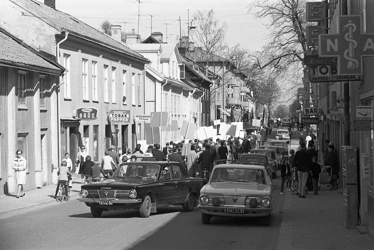 1:a majtåg. Hela demonstrationståget bakifrån. Demonstranter, med plakat, trängs med bilarna på Nygatan. Cyklar och barnvagnar hålls åt sidan. På vänster sida, av gatan, ligger HåGes Bröd, Frisören, Folkes Tobak och Papper, samt begravningsbyrån PN Styrud. På höger sida syns Apoteket, Tobaksaffären, EPA, en bar samt bokhandeln.