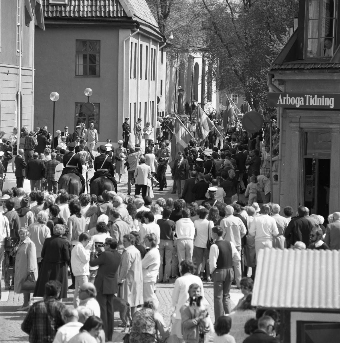 Allmänheten, en fanborg och ett stort pressuppbåd möter kungaparet som kommer gående på Rådhusgatan. Drottning Silvia har en blombukett i hänerna. Ridande poliser har kontroll. Dörren till Arboga Tidning står öppen. Heliga Trefaldighetskyrkan skymtar i bakgrunden.