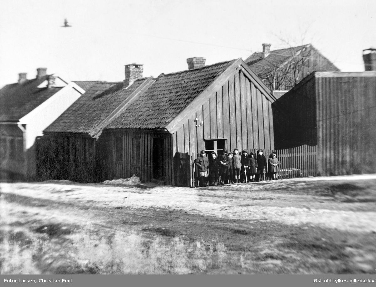 """Aarslandsgården  eller Aarslandsstua i Glengsgata 16 i Sarpsborg fra før 1926. Gruppe med barn (ukjente) stilt opp utenfor huset. Til høyre garver Jensens garveri. Påskrift: """"I bakgrunnen ses til høire garver Jensens garveri. Da Aarslandsgaarden blev flyttet til museet ble dette revet i forbindelse med anlegget i Aarslands gate """" I starten var det høkeri i bygningen, deretter butikk, bygd i tre faser, lå på hjørnet av Glengsgata og Torsbekkgata i Sarpsborg, flyttet til Borgarsyssel Museum i 1926."""