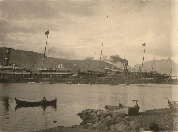 Motivet viser DS JUPITER (bygget 1856) ved en kai i Nord-Norge. Et annet dampskip fra DBS ligger også til kais, og kaien er full av varer og pasasjerer. I forgrunnen en mann i robåt og flere robåter på land og fortøyd langs bryggen.