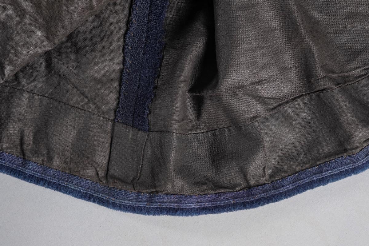 Langt blått skjørt med lomme. Innvendig foret med sort stoff. I livet er det en hempe av sort stoff. Lukkes med to hekter og hemper i livet. Festet til kjolelivet med hemper. Nederst på skjørtet er det en forsterkningskant med en blå slitelist av bånd og floss.