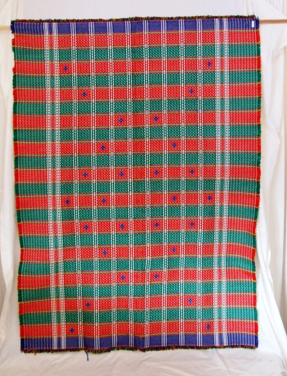 Mønster i striper. Små blå diamamtmønster rundt i kring på teppet.