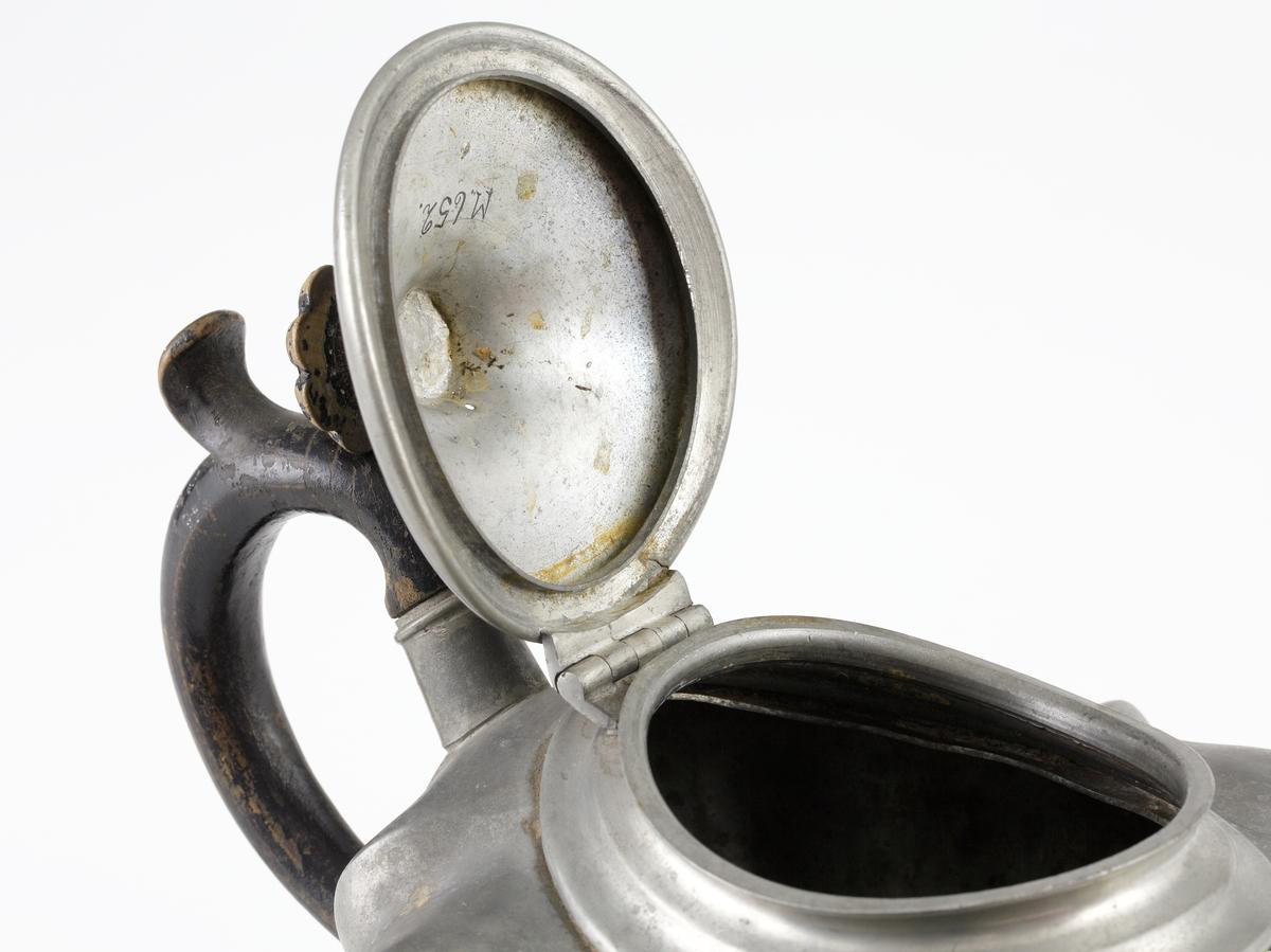 """Tekanna av tenn.  Konisk modell med rund fotring. Raka åsar på livet. Uppsvängd pip med sil vid basen (inuti kannan). Locket har en neddragen oval form samt försett med gångjärn och svarvad knopp av svärtat trä. På kannans liv sitter det svängda trähandtaget infattat i två fastlödda rörbitar. I kannans botten står: """"S, SHAW & FISHER SHEFFIELD, 1103""""."""