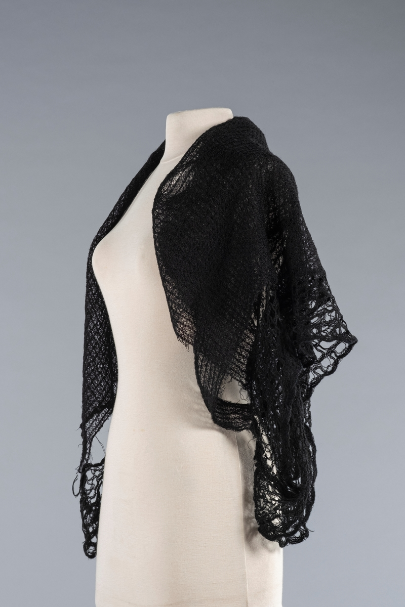 Sort hullmønstret sjal i bomullstråd. Noen store hull i sjalet. Påsydd kant med samme tråd, men med ulikt mønster. Muligens brukt sprangteknikk i den påsydde kanten. Kanten er ca 8. cm bred og har begynt å løsne fra sjalet.