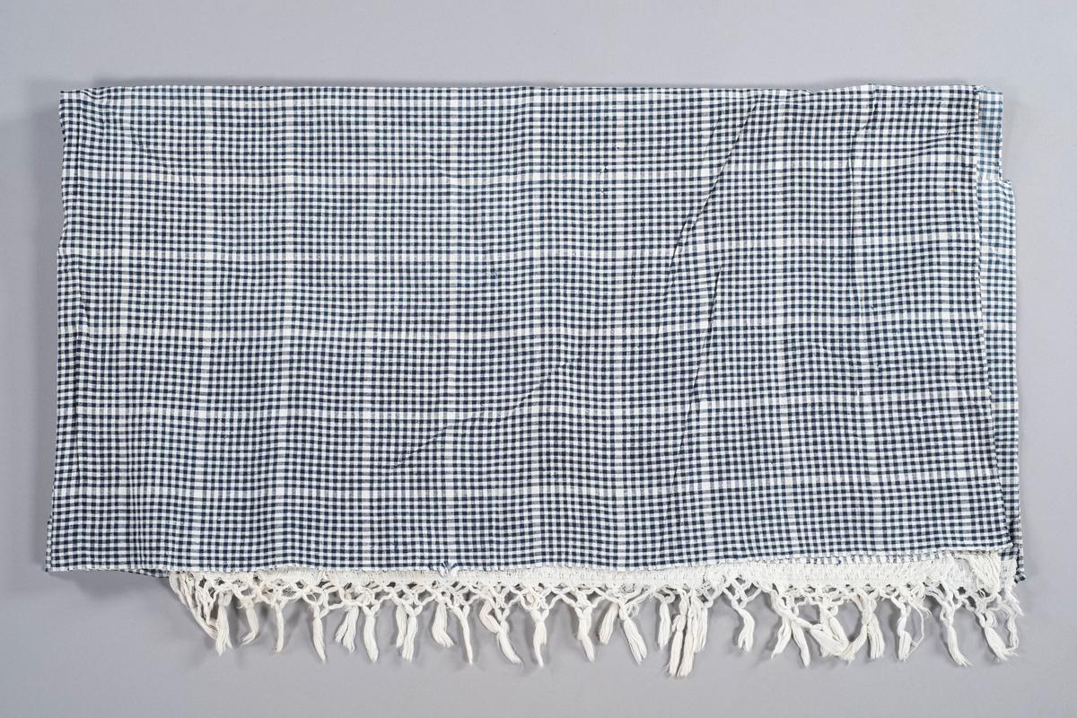 Hvit- og blårutet del av sengeomheng i bomull. Sydd sammen av tre stykker stoff. Hvite frynser nederst i ene kanten.