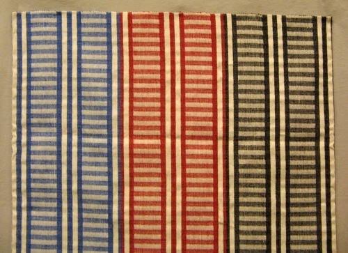 Ett stadigt vävprov på överkast i inslagsförstärktkypert med tre olika inslagsfärger, svart, röd och blå. Det är tvärrandigt med 70 mm höga staplar. Varpen är av tvåtrådigt bomullsgarn. Inslaget är av halvblekt entrådigt lingarn och färgat entrådigt ullgarn, möbeltygsgarn.  Vävprovet är märkt R30:1 på ett vitt bomullsband.  Vävprov med modellnamn Randhild är formgivet av Ann-Mari Nilsson och tillverkat av Länshemslöjden Skaraborg. Det finns med  på sidan 70-71 i vävboken Inredningsvävar av Ann-Mari Nilsson i samarbete med Länshemslöjden Skaraborg från 1987, ICA Bokförlag. Se även inv.nr. 0001-0029,0031-0040.