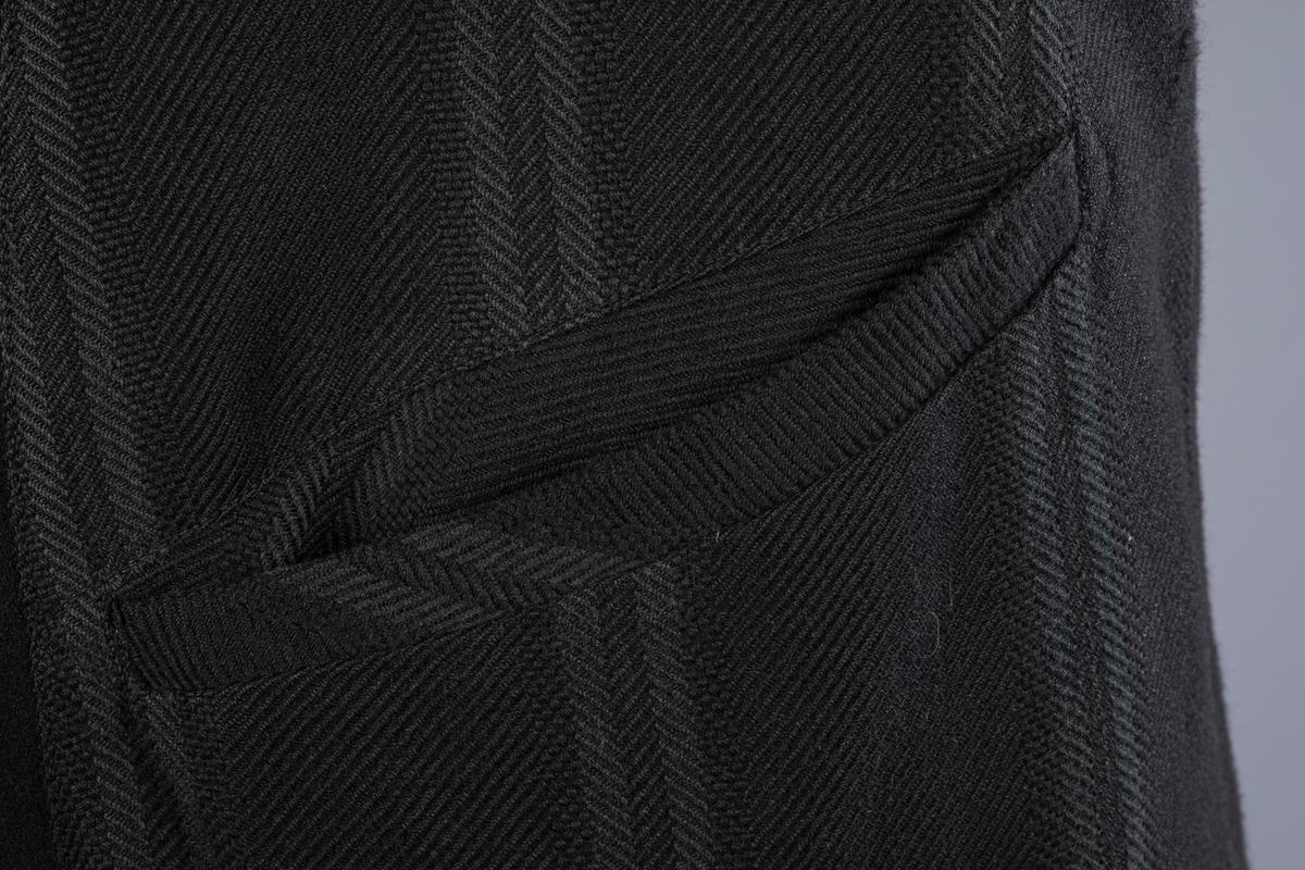 Ullfrakk, to rader med tre knapper i front, Grønt og svart innerfôr. Silkeaktig fôr i ermene. I nakkelinninga er det en metallhempe til oppheng. Innerlomme høyre side. To lommer på utsida, samt en brystlomme. Splitt bak.