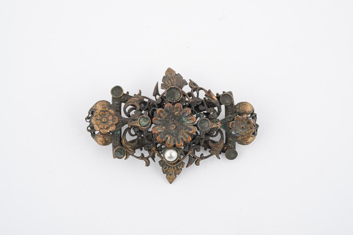 En brosje med blomster og akantus. Det har tidligere vært pålimt 8 perler, det er én som gjenstår. Nålen mangler.