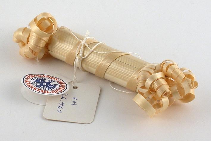 En cylinderformad smällkaramell med krusade halmstrån i vardera ändar.