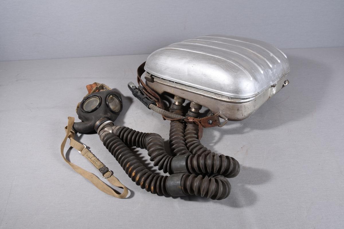 Bærbart gassbeskyttelsesapparat, består av en metallbeholder med ryggseler og magesele. Manometer med slange fra beholderen. Beholderen har løst lokk hengslet i toppen. Innholdet i boksen er knyttet til slanger og pustemaske på utsiden av beholderen gjennom koblinger. Koblingene har regueringsmulighet.