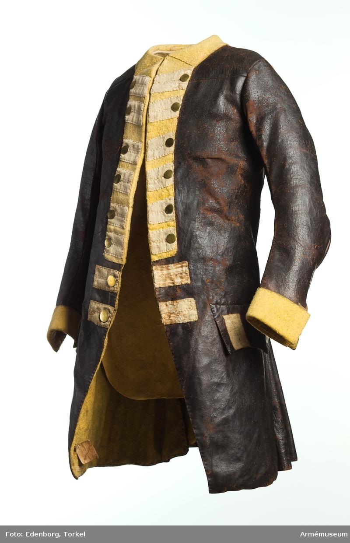 """Grupp C I. Av brunt läder med gul krage och rabatt med vita """"knapphål"""" av redgarn. Fickorna är fasonerade med stående """"knapphål"""" Gula uppslag. Över klocksprundet bak ett vitt redgarnsband.  En jämförelse med Jacob Gillbergs uniformsritningar av uniform m/1765 visar att den har samma dekorerade bröstrevärer och knapphål som Livgardet till fots rockar. Detta bör då vara en rock m/1765 för Livgardet till fot, men utförd i skinn istället för kläde. Möjligtvis rör det sig om någon form av rock för vakttjänst. 2010-05-17 MM."""