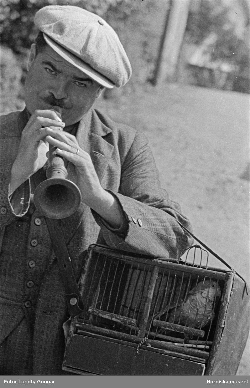 Motiv: Kullabygden; (ingen anteckning) ; Detalj av byggnad, stenmur vid hus, vy med gata, människor på en pir, människor tittar på ett fartyg i bakgrunden, ett fartyg vid en kaj, porträtt av en kvinna som håller ett barn, en man håller en bur med en fågel, en man spelar säckpipa, en man spelar skalmeja. Enligt uppgift från Bengt Edqvist 2018 kallas säckpipan zampogna och skalmejan ciaramella och papegojan drog ett slags lyckokort ur en kortlek.