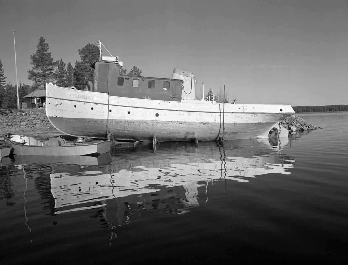 Sjøsetting av slepebåten Trysilknut fra Sørlistøa ved Osensjøen i mai 1984. Dette fartøyet ble trukket opp på slipp når fløtingssesongen, og der ble den stående vinteren over, inntil forberedelsene til neste fløtingssesong startet. På slippen sto Trysilknut på ei vogn, som kunne beveges opp og ned fra vannet på jernbaneskinner.  Avstanden mellom de ytterste skinnene var 360 centimeter. Da Trysilknut kom ut i vannet brukte fløterne varpebåtene til å trekke den tunge slepebåten av vogna den hadde stått på gjennom vintersesongen. Dette fotografiet ble tatt idet Trysilknut var vinsjet ned mot vannspeilet, men før den var kommet så langt at fløterne kunne starte arbeidet med å trekke den av vogna. Vi ser en av varpebåtene som skulle brukes i dette arbeidet til venstre i forgrunnen. Bak baugen på slepebåten skimter vi deler av kontor- og sovebrakka på Sørlistøa.   Osensjøen har et nedslagsfelt på 1 300 kvadratkilometer, hvorav om lag halvparten er bevokst med produktiv skog, og i dette området vokser det mye kvalitetsvirke.  Fra gammelt av var fløtinga her et samspill mellom strømdrag i sjøen, vinden og menneskelig muskelkraft.  Lenge ble stokkene samlet i flåter og forsøkt seilt mot Valmen og avløpselva Søndre Osa, noe som innebar vanskeligheter når det var vindstille eller motvind.  Utover på 1800-tallet begynte man å bruke spillflåter med gangspill, forankret i «dregger» (ankere) med lange trosser.  Denne formen for fløting la beslag på mye mannskap, og med stigende lønninger ble det en kostnadsfaktor tømmerkjøperne gjerne ville krympe.  I 1913 foreslo fløtingsdirektør Johs. Johannesen for styret i Christiania Tømmerdirektion (seinere Glomma fellesfløtingsforening) at organisasjonen skulle kjøpe en «slæpedamper» til fløtinga på denne innsjøen. Med denne investeringa antydet han at de årlige driftskostnadene kunne redusere driftskostnadene til snaut 40 prosent av hva de hadde vært. Styret gikk inn for saken – man ville få bygget en dampslepebåt til fløtinga på denne inn