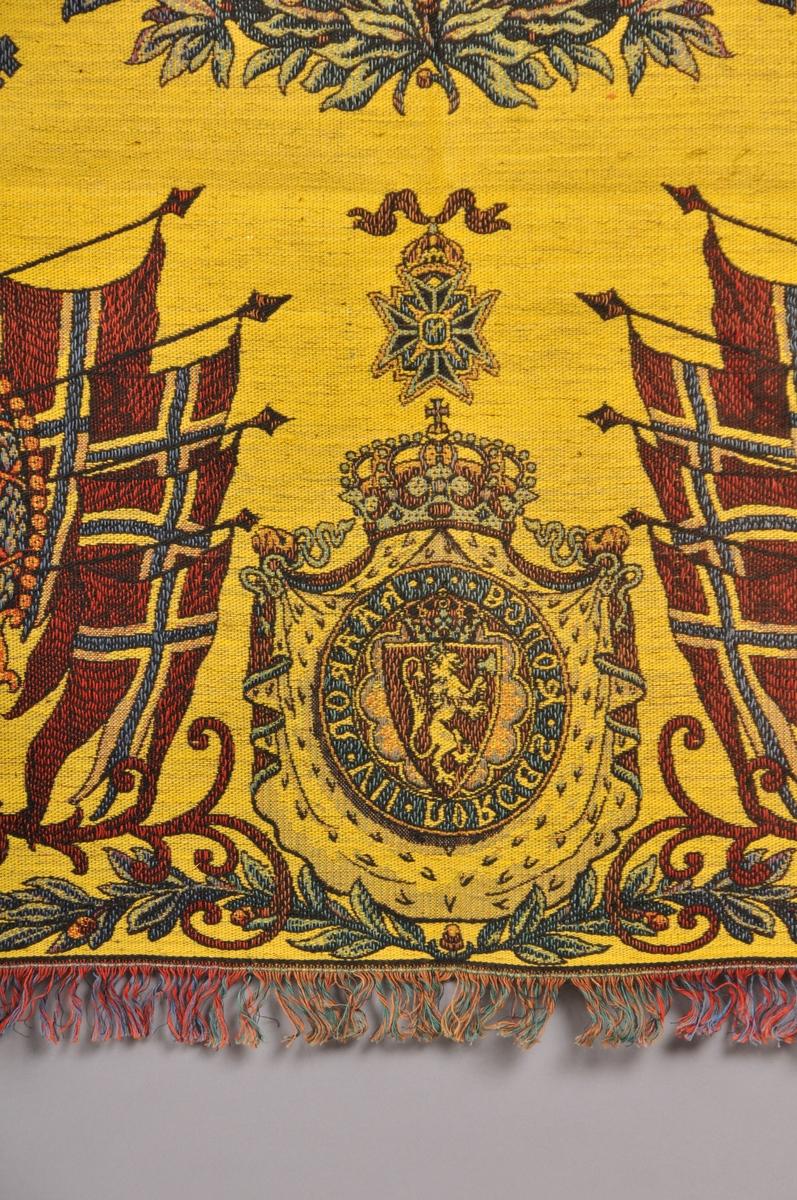 """Tekstil i bomull med litt metalltråd. Fleire fargar. Portrett av HaakonVII på midten. I kvart hjørne er der portrett av Kong Haakon, Dronning Maud og Kronprins Olav. Den norkse løva med teksten """"Haakon VII Norges Konge"""", Flagg, ranker og løver m.m. Tafs kring alle kantane. Tafset er ein forlengelse av varp og verft. Tydeleg rett og vrangside. God stand, men noko bleika på den eine sida."""
