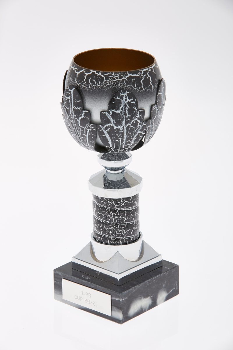 Statuettligningnende pokal i metall med base av marmorert stein. Kule på toppen med blader utenpå.