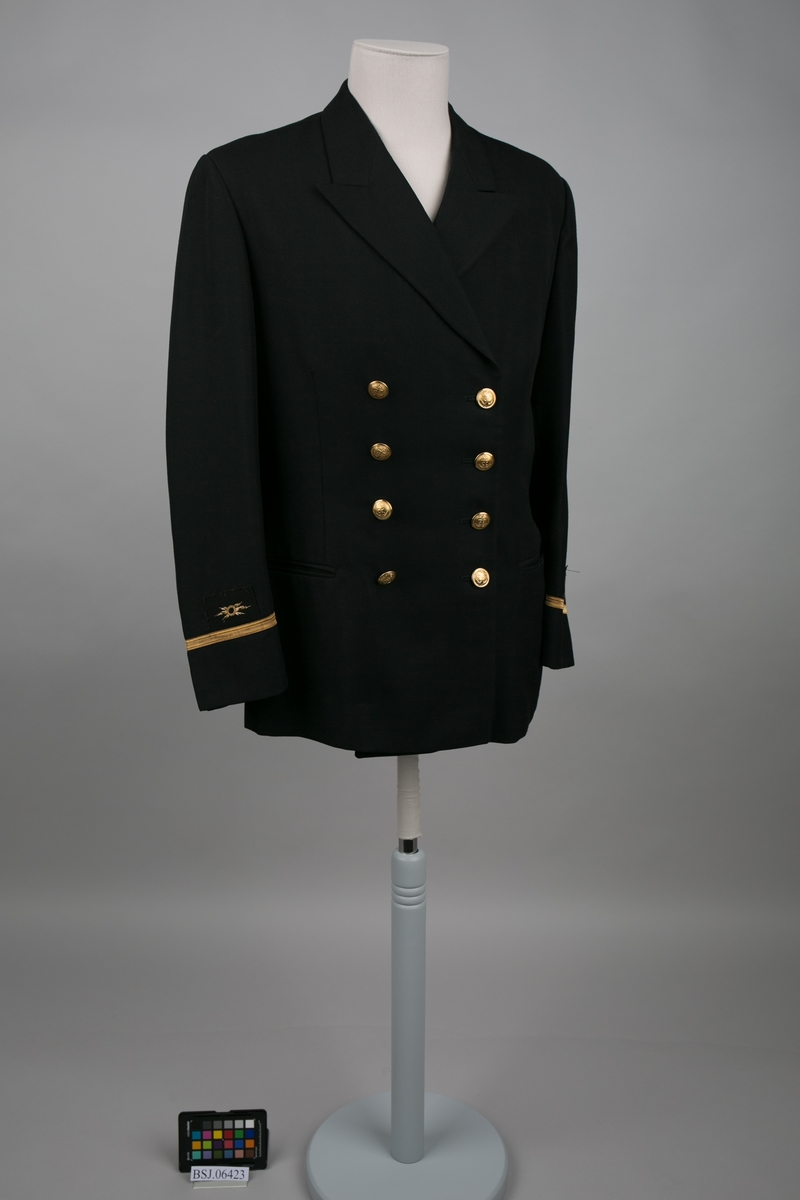 Telegrafist uniformjakke med 1 stk. gullbånd og distinksjoner på erme og slag krage. Dobbelspent med til sammen 8 stk. knapper i gullfarge med motiv av anker.