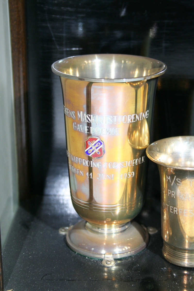 Pokal med innskrift og rederiflagg på siden. Pokalen er skrudd fast til bunnen i monteren med tre klemmer.