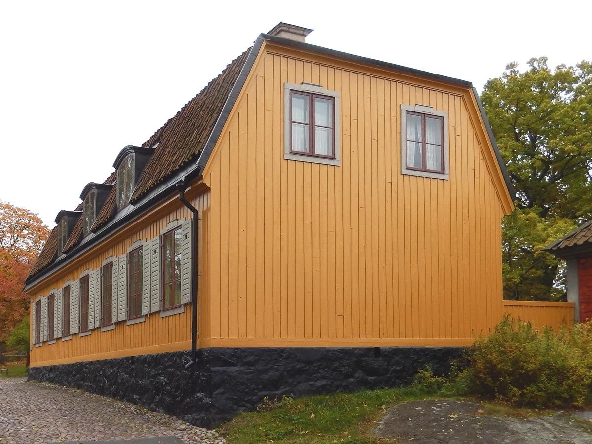 """Hazeliushuset på Skansen är en timrad byggnad i en våning med inredd vind. Fasaden har stående profilerad locklistpanel målad med gul linoljefärg. Fönstersnickerierna är målade med linoljefärg i engelskt röd, fönsterluckorna är grå. Taket är brutet och valmat, klätt med enkupigt lertegel. På varje takfall finns tre takkupor med fönster upptagna. Skorstenarna är tre, murade och putsade.  Entrén är vänd mot gården och försedd med en stentrappa samt baldakin i bemålad plåt.  Byggnaden låg tidigare på Surbrunnsgatan i Stockholm, i det kvarter som nu avgränsas av Odengatan, Sveavägen, Surbrunnsgatan och Hagagatan.   I huset föddes Skansens grundare Arthur Hazelius den 30 november 1833. Byggnaden skänktes av sällskapet """"Vänner till Pauvres Honteaux"""" 1916 och flyttades till Skansen 1926."""