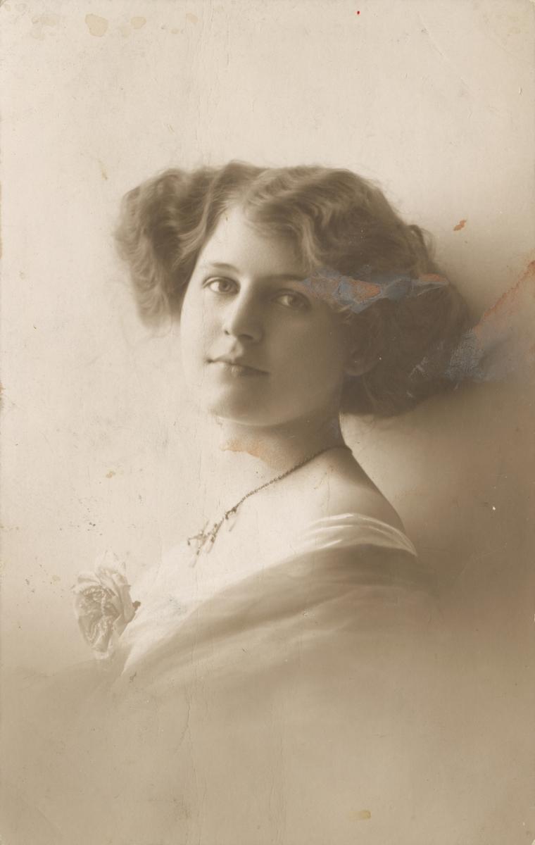 Postkortmotiv av ei ung kvinne med halskjede og rosett.